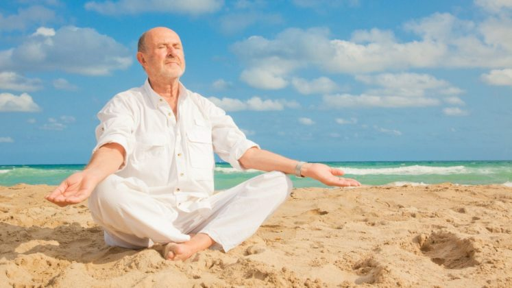 homme faisant du yoga sur la plage
